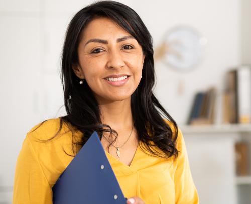 Latina with clipboard smiling at the camera