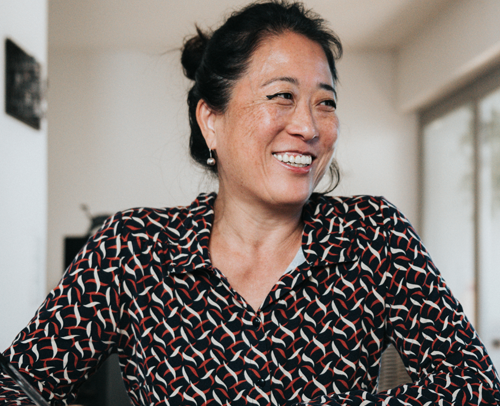 An Asian woman sitting a desk looking to the right and smiling