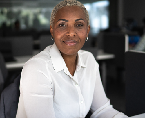 Black woman sitting at a desk in an office smiling at the camera