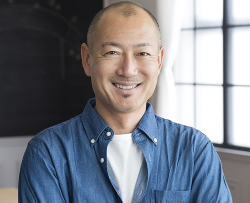 An Asian man in an office smiling at the camera