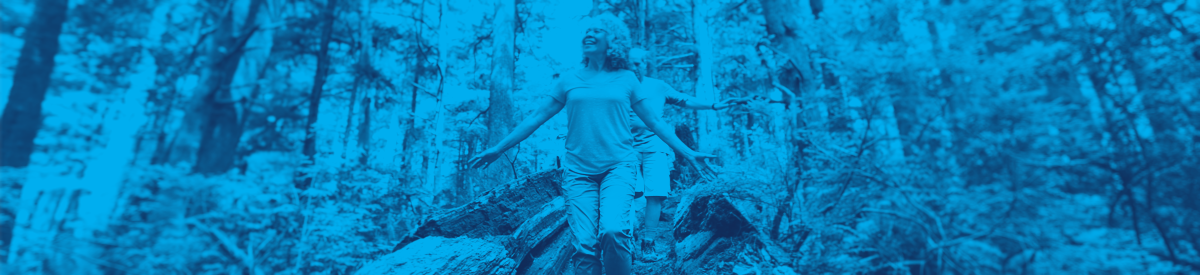 Older woman walking among tall trees